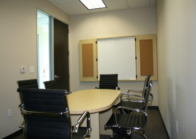 Conference room has white board for writing, projector and white screen for main seating up to 8 people